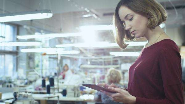 Young woman is standing in a clothing factory and using a tablet while employees work in the background. Royalty-free stock video