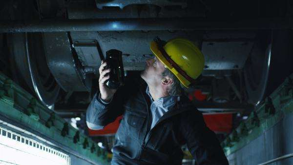 Technician in hard hat with flashlight in hand inspecting train Royalty-free stock video