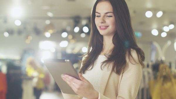 Happy young brunette girl is standing in a department store and using a tablet computer. Royalty-free stock video