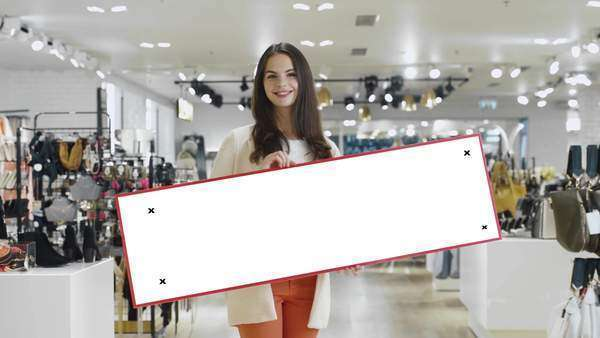 Young smiling brunette woman is holding a blank mock-up sign in a department store. Royalty-free stock video