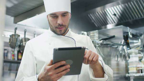 Professional chef in a commercial kitchen is using a tablet computer. Royalty-free stock video