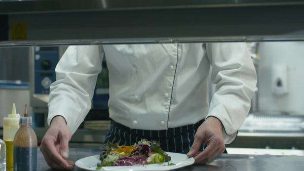 Happy professional chef in a commercial kitchen is garnishing and serving salad. Royalty-free stock video