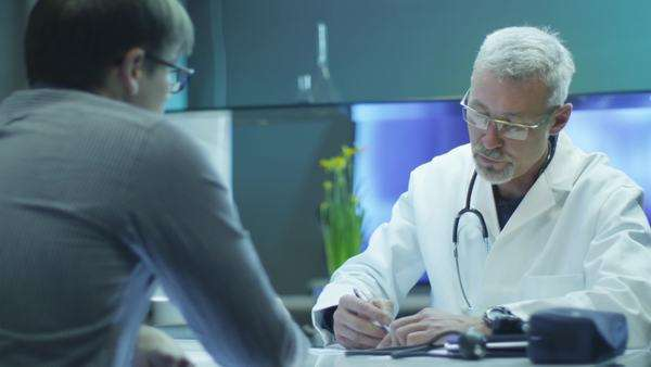 Doctor is writing out prescription for patient. Royalty-free stock video