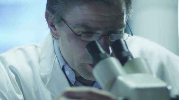 Scientist does research and looks through microscope Royalty-free stock video