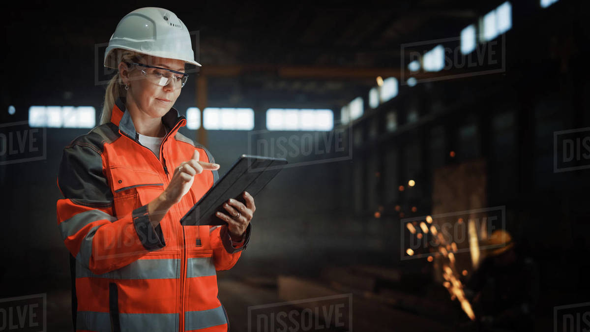 Professional Heavy Industry Engineer/Worker Wearing Safety Uniform and Hard Hat Uses Tablet Computer. Serious Successful Female Industrial Specialist Standing in a Metal Manufacture Warehouse. Royalty-free stock photo