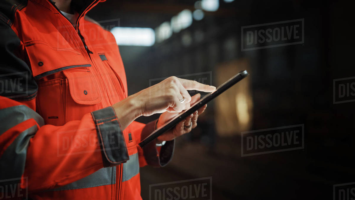 Close Up on Hands of a Professional Female Heavy Industry Engineer Wearing Safety Uniform and Using Tablet Computer. Industrial Specialist Standing in a Metal Construction Manufacture. Royalty-free stock photo