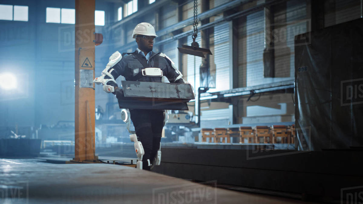 Black African American Engineer is Testing a Futuristic Bionic Exoskeleton and Proudly Wearing it in a Heavy Steel Industry Factory. Powered Mobile Machine Shell made for Helping Workers. Royalty-free stock photo