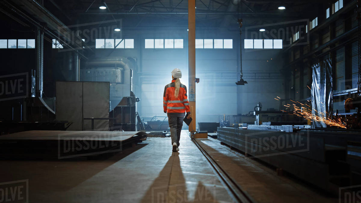 Professional Heavy Industry Engineer/Worker Wearing Safety Uniform and Hard Hat Uses Tablet Computer. Serious Successful Female Industrial Specialist Walking in a Metal Manufacture Warehouse. Royalty-free stock photo