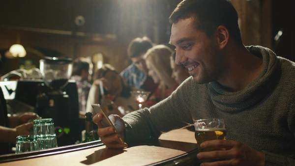 Happy man holds a glass of beer while using a smartphone in a bar. Royalty-free stock video