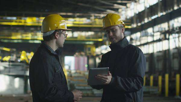 Engineer and worker have conversation in foundry. engineer using tablet. Royalty-free stock video