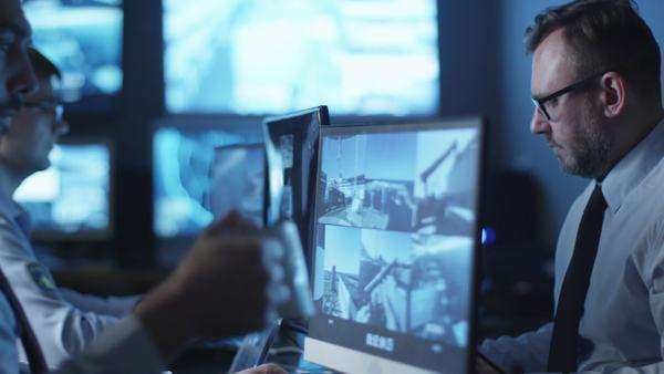 Group of security officers are working in a dark monitoring room filled with display screens. Royalty-free stock video