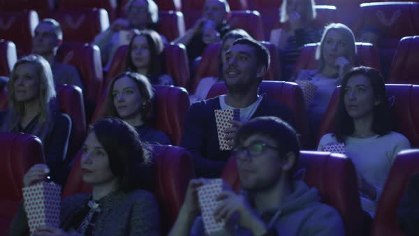 Man is taking his seat while people are watching a film screening in a movie cinema theater. Royalty-free stock video