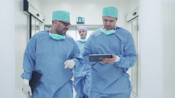 Two doctors walking through hospital and chatting, holding tablet in hands. Royalty-free stock video