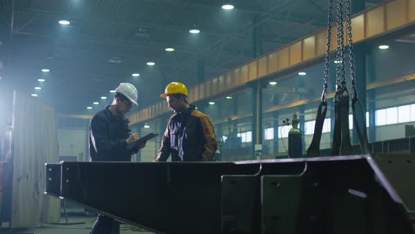 Manager and engineer worker in hardhats are having a conversation in a heavy industry factory. Royalty-free stock video
