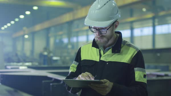 Engineer in hardhat is using a tablet computer in a heavy industry factory. Royalty-free stock video
