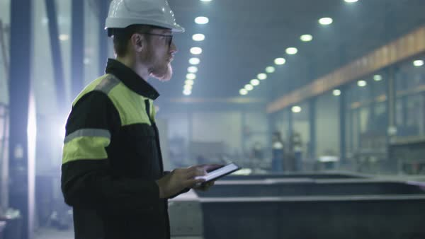 Engineer in hardhat is moving through a heavy industry factory with a tablet computer. Is greeting a worker with a handshake. Royalty-free stock video