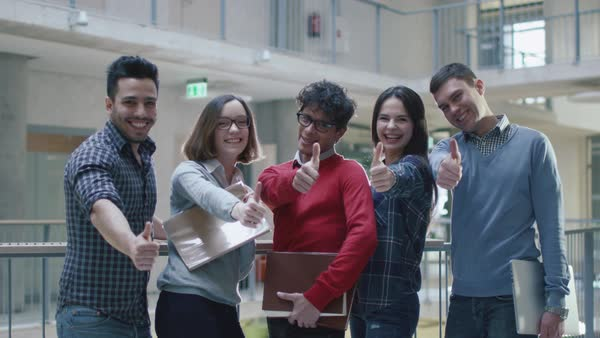 Group of happy young multi-ethnic students are showing thumbs-up in a college building. Royalty-free stock video