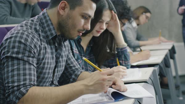 Footage of hispanic student writing with pen on paper in a collage classroom during lecture. Royalty-free stock video
