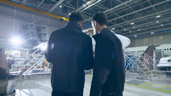 Aircraft maintenance worker and engineer having conversation. Looking at the airplane. Royalty-free stock video