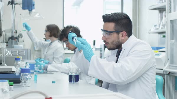 Team of students in coats working in laboratory of chemistry classroom. Royalty-free stock video