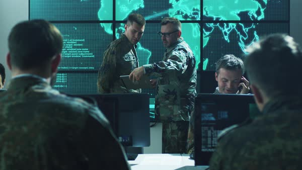 Group of military IT professionals on briefing in monitoring room filled with displays on military base Royalty-free stock video