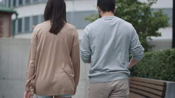 Follow shot of young woman and man are walking and talking in urban environment. Royalty-free stock video