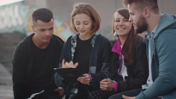 Group of smiling and laughing teenagers using tablet computer for entertainment outdoors in urban environment. Royalty-free stock video