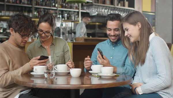 Group of young people using phones in coffee shop. Royalty-free stock video