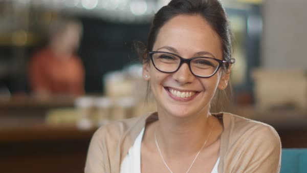 Portrait of attractive smiling young woman at cozy coffee shop. Royalty-free stock video