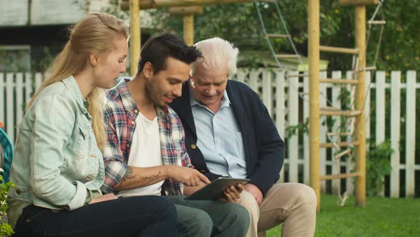 Young People Teaching Senior Man how to Use a Tablet Computer Outdoors. Royalty-free stock video