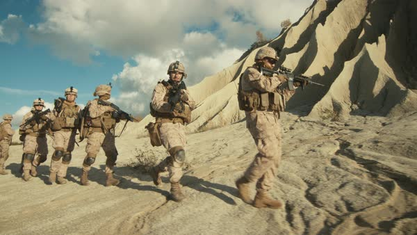 Squad of Fully Equipped and Armed Soldiers Walking in Single File in the Desert. Royalty-free stock video