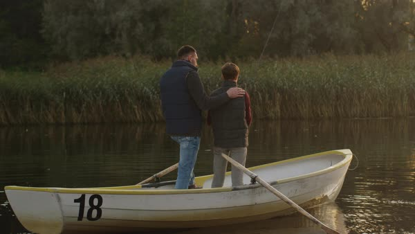 Father and son are standing in the boat and fishing Royalty-free stock video