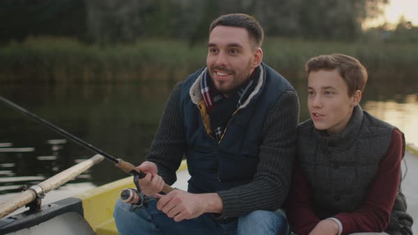 Father and son sitting in the boat fishing. Father swings fishing rod Royalty-free stock video