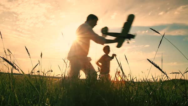 Father and son are playing and running with model airplane in the field Royalty-free stock video