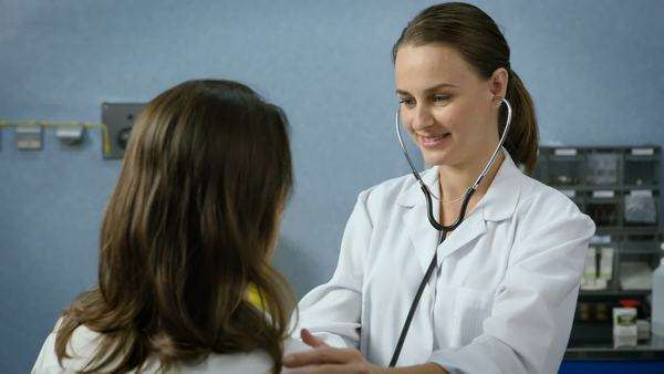 Young adult female doctor examining a patient using a stethoscope Royalty-free stock video