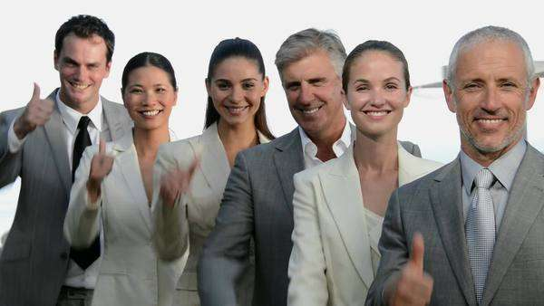 Business team of six people in a line turning head to face camera then smiling and gesturing thumbs up. Royalty-free stock video