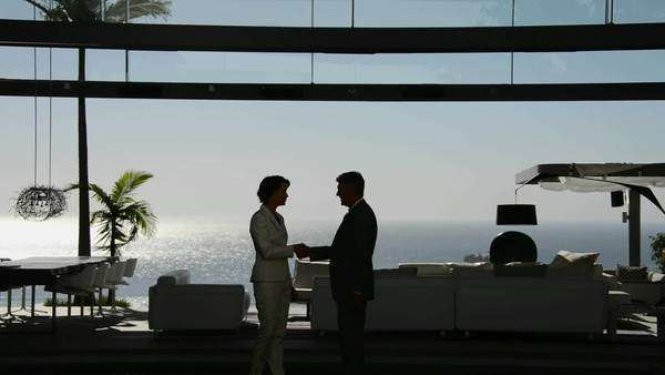 Businessman and businesswoman meeting and shaking hands in a luxury living room overlooking the sea. Royalty-free stock video