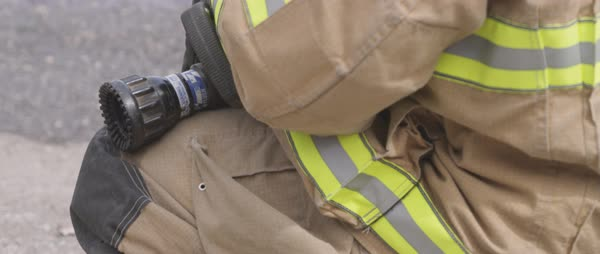 Hand-held shot of a crouching fireman holding a fire hose Royalty-free stock video