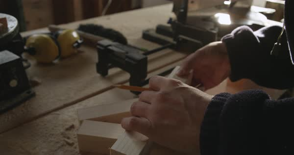 Hand-held shot of a carpenter marking wood with a pencil Royalty-free stock video