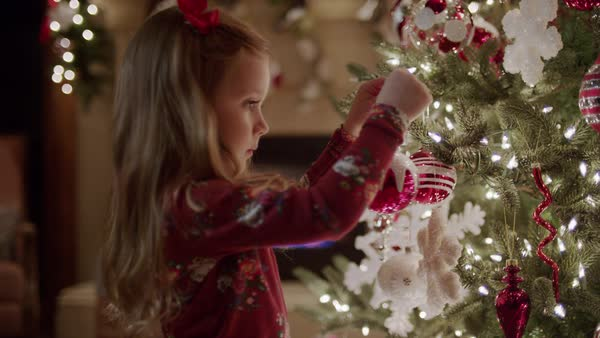 Medium panning shot of family decorating Christmas tree Royalty-free stock video
