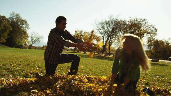 Medium shot slow motion of Young man and young woman throwing leaves in park Royalty-free stock video
