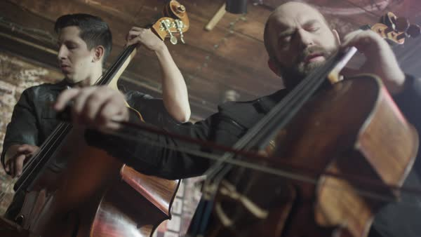 Medium panning low angle view of men playing bass and cello in bar Royalty-free stock video