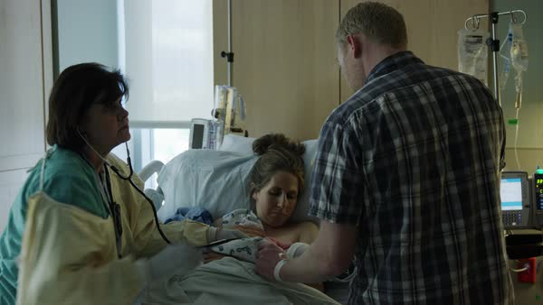 Medium panning shot of nurse and parents of newborn in hospital Rights-managed stock video