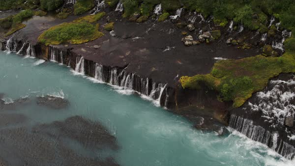 Wide high angle panning shot of waterfalls pouring into river Royalty-free stock video