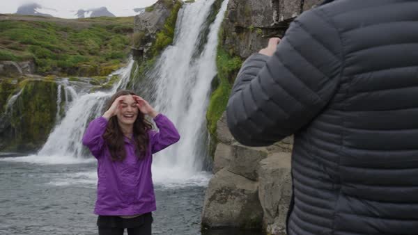 Medium panning shot of man photographing woman near waterfalls Royalty-free stock video