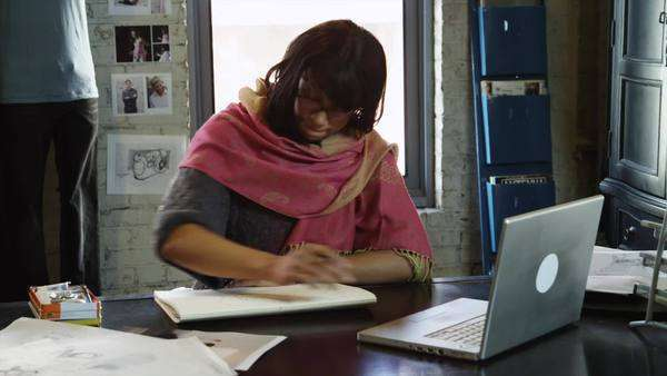 Medium dolly shot of PAN Young woman using laptop and note pad working in office, Salt Lake City, Utah Royalty-free stock video