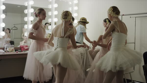 Medium shot of smiling ballerinas talking in dressing room Rights-managed stock video