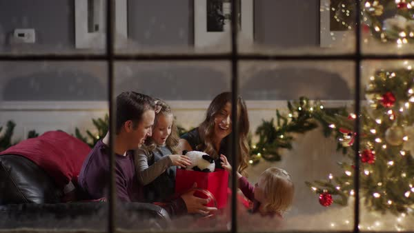 Medium zoom in shot of girl opening Christmas gift behind window Royalty-free stock video