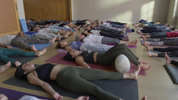 Wide slow motion panning shot of yoga students in corpse pose Royalty-free stock video