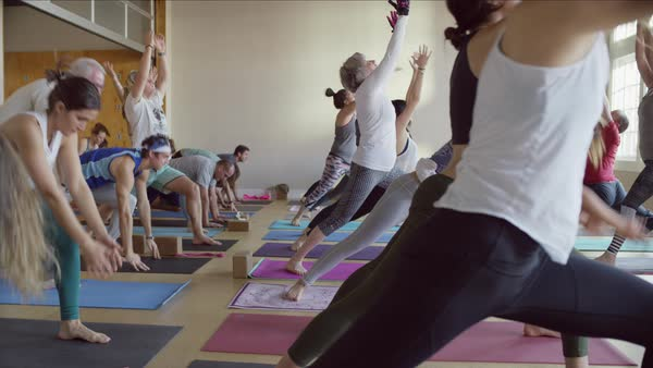 Medium slow motion panning shot of instructor leading yoga class Royalty-free stock video